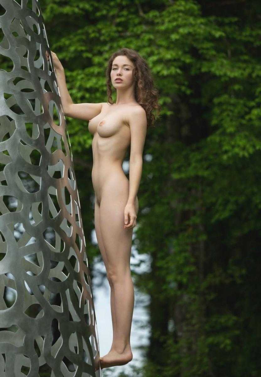 Полностью голая девушка стоит у дерева